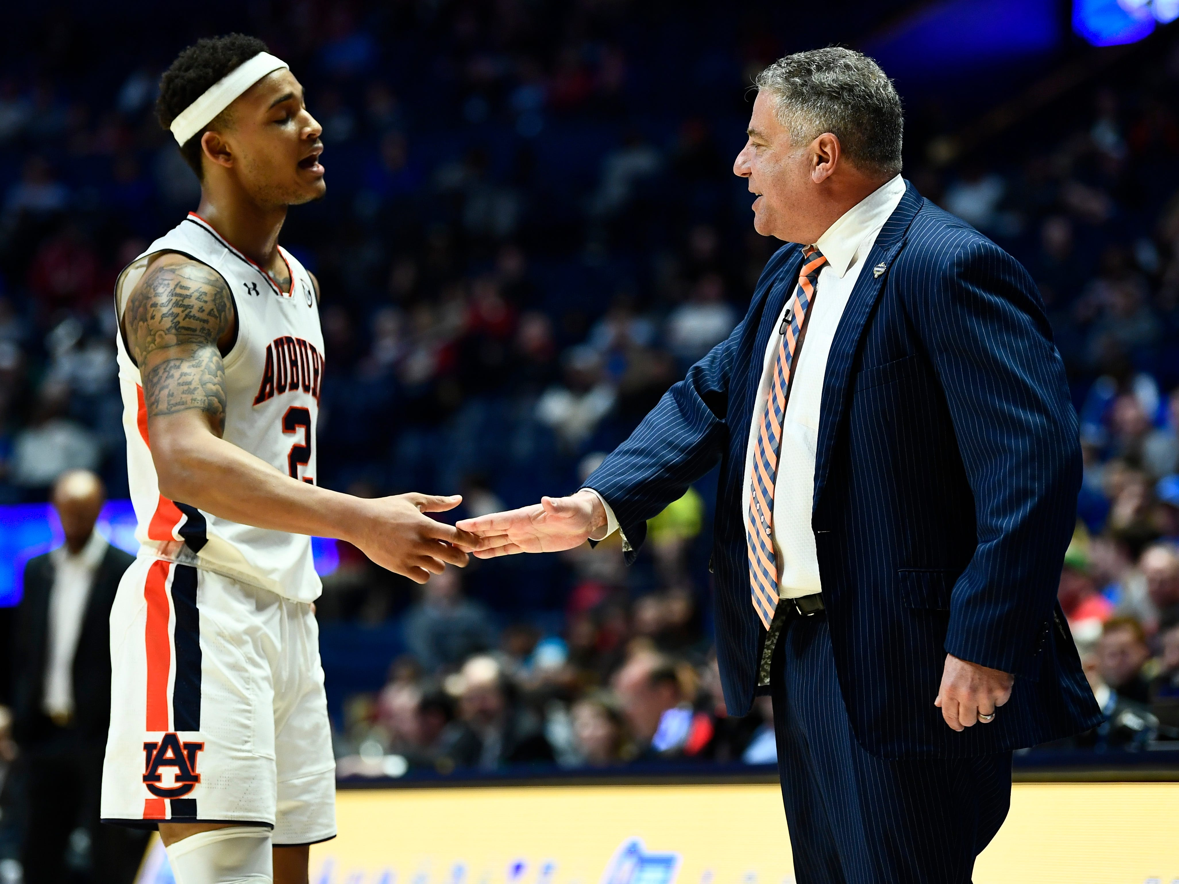 Auburn head coach Bruce Pearl shakes hands with Auburn guard Bryce Brown (2) during the second half of the SEC Men's Basketball Tournament game at Bridgestone Arena in Nashville, Tenn., Thursday, March 14, 2019.