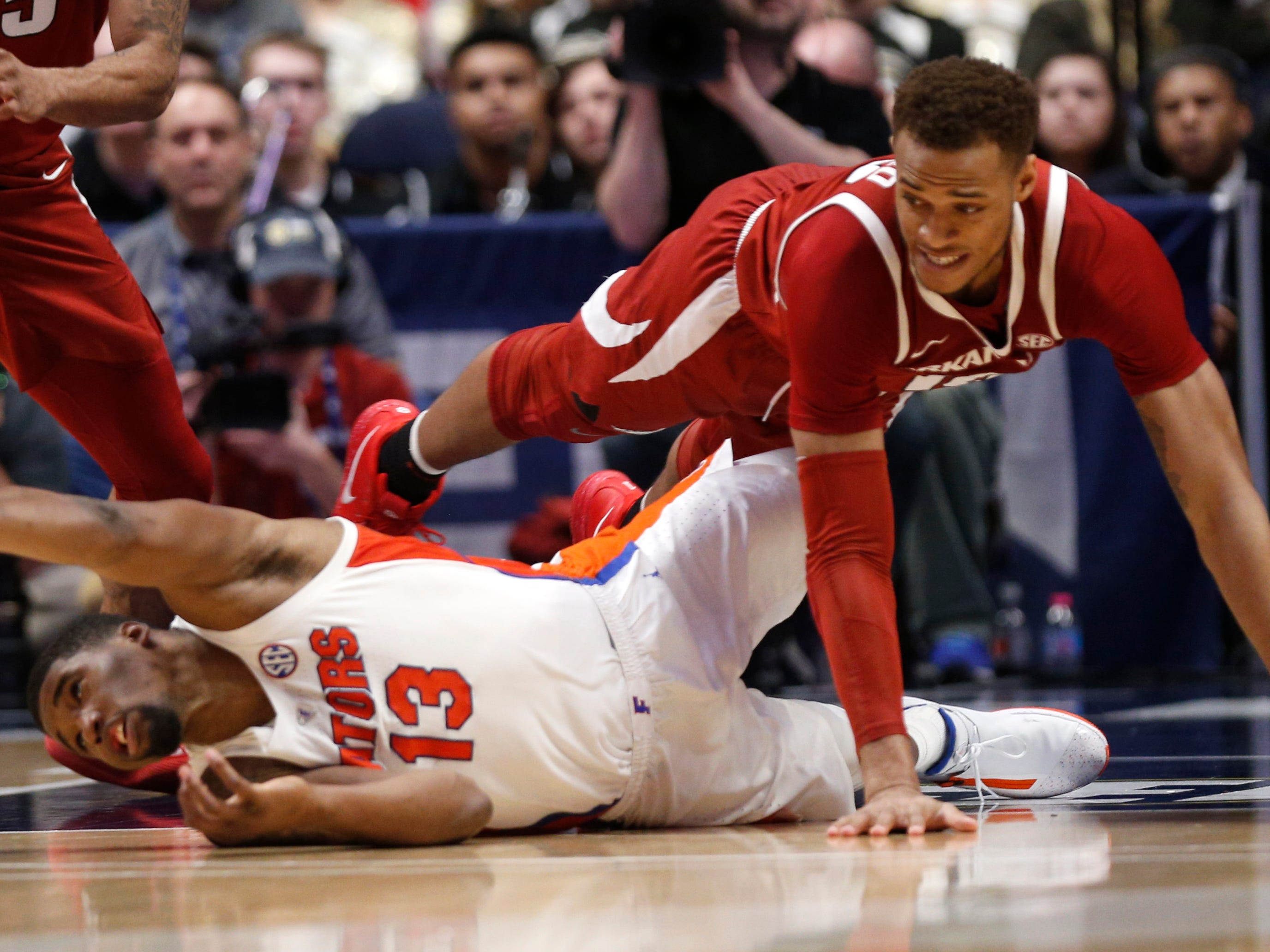 Florida center Kevarrius Hayes (13) and Arkansas forward Daniel Gafford (10) battle for a loose ball during the second half of the SEC Men's Basketball Tournament game at Bridgestone Arena in Nashville, Tenn., Thursday, March 14, 2019.