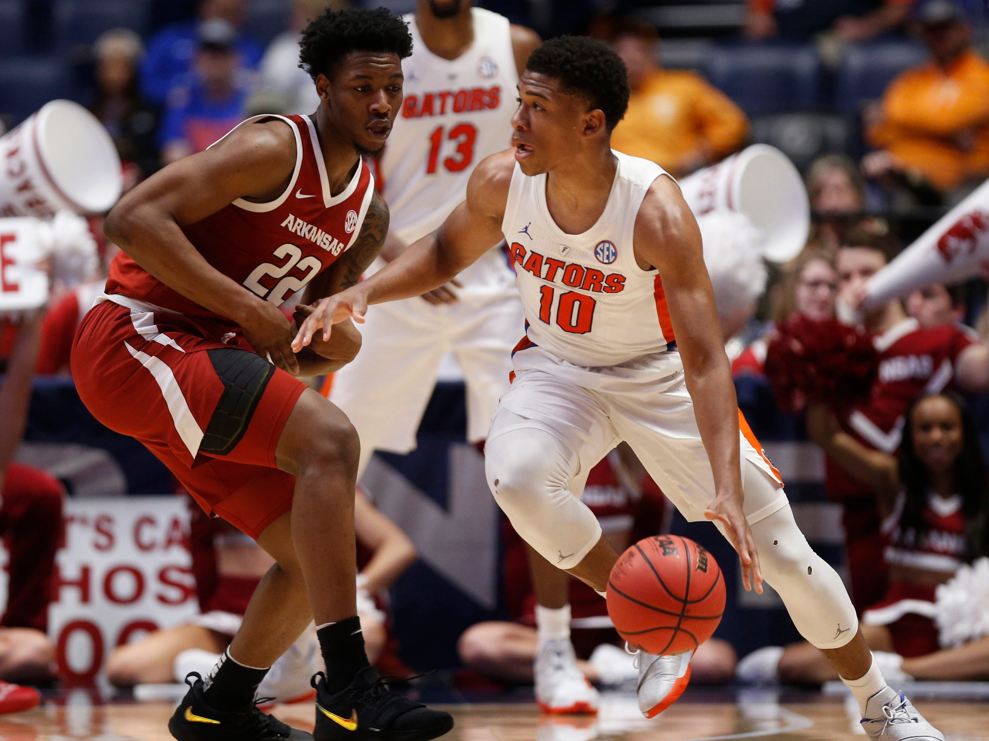 Florida guard Noah Locke (10) moves the ball defended by Arkansas forward Gabe Osabuohien (22) during the first half of the SEC Men's Basketball Tournament game at Bridgestone Arena in Nashville, Tenn., Thursday, March 14, 2019.
