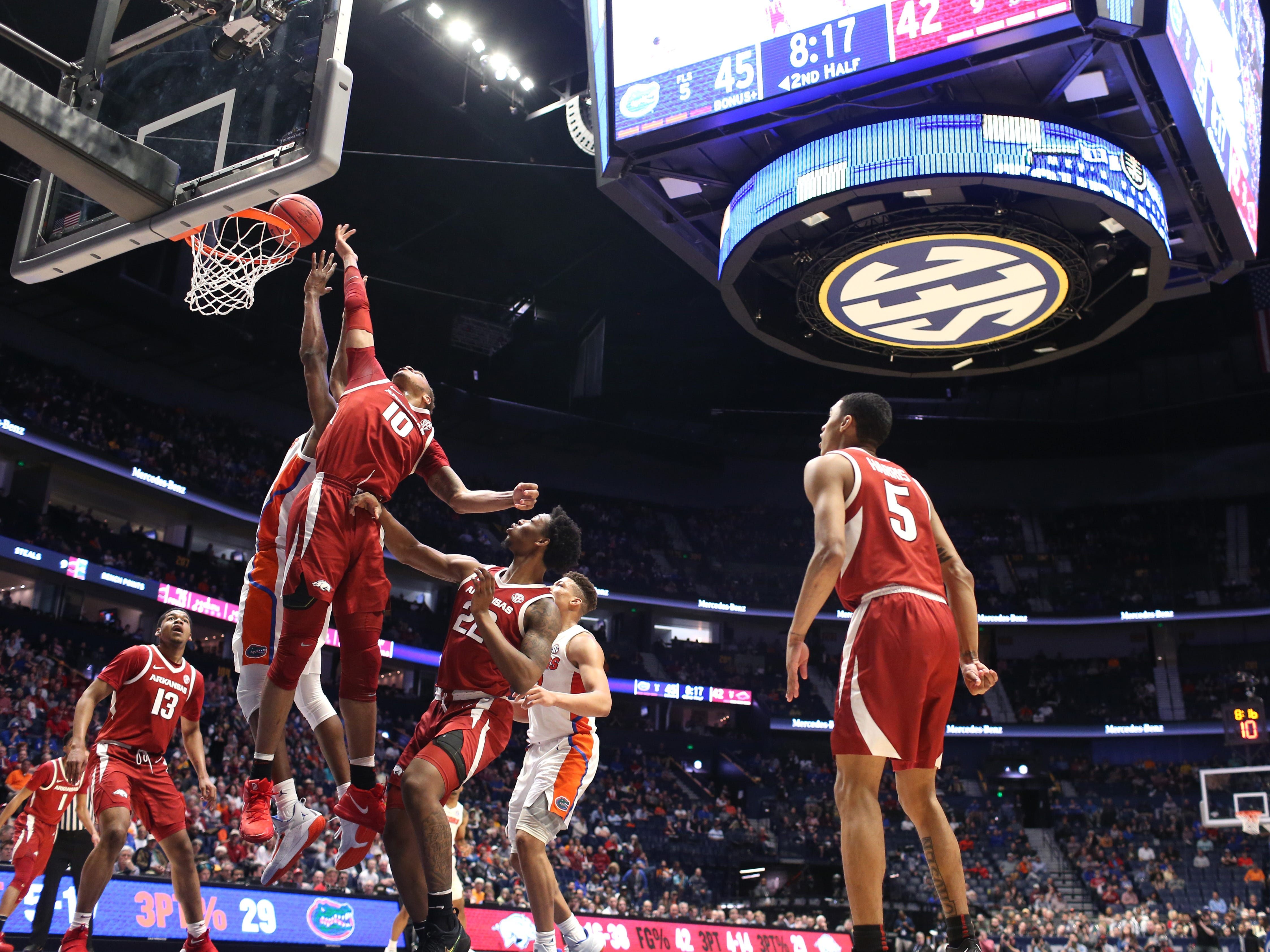 Florida and Arkansas battle under the Gator basket during the second half of the SEC Men's Basketball Tournament game at Bridgestone Arena in Nashville, Tenn., Thursday, March 14, 2019.