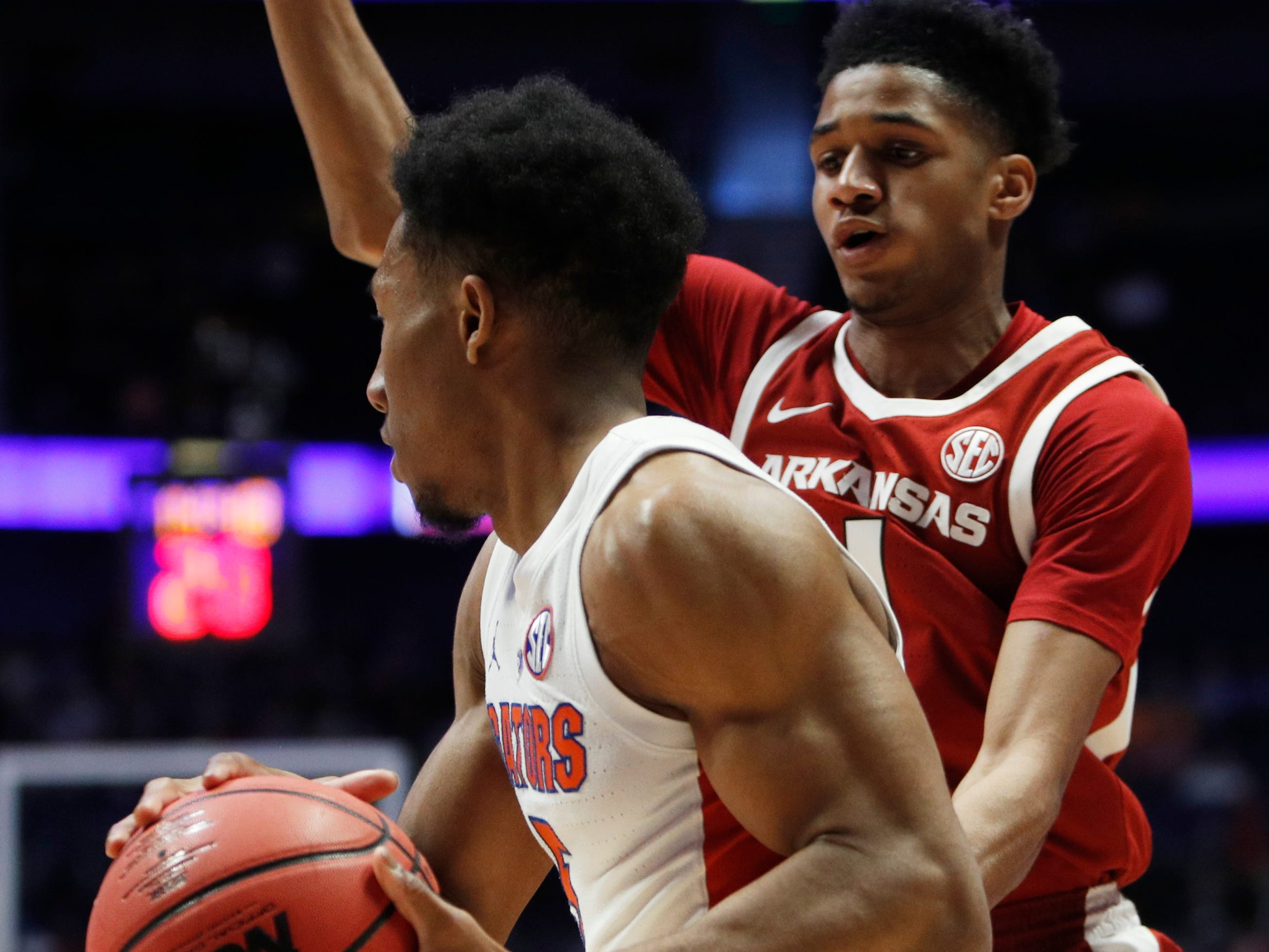 Florida guard KeVaughn Allen (5) tries to move the ball defended by Arkansas guard Isaiah Joe (1) during the first half of the SEC Men's Basketball Tournament game at Bridgestone Arena in Nashville, Tenn., Thursday, March 14, 2019.
