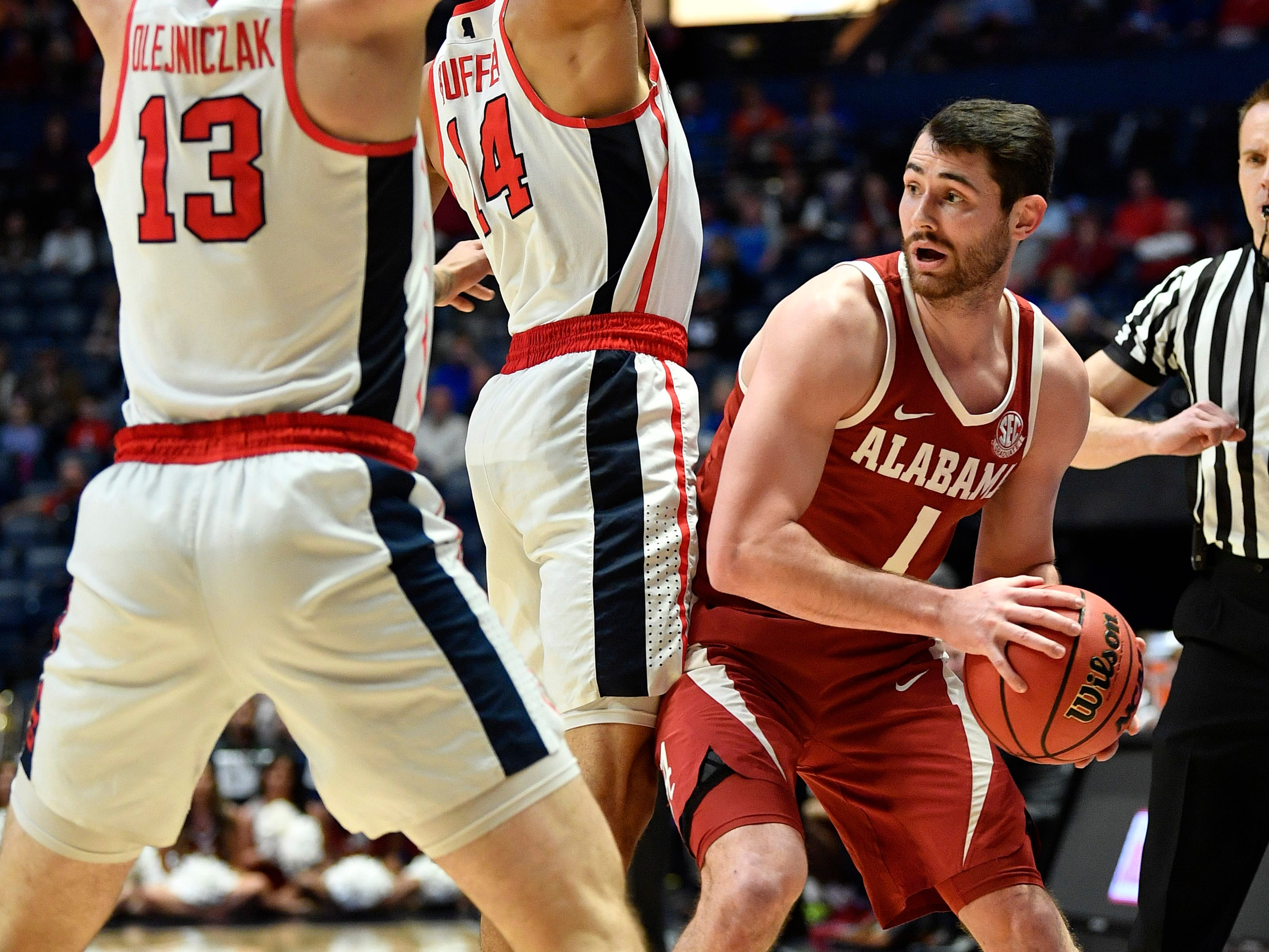 Alabama guard/forward Riley Norris (1) is defended by Ole Miss center Dominik Olejniczak (13) and forward KJ Buffen (14) during the first half of the SEC Men's Basketball Tournament game at Bridgestone Arena in Nashville, Tenn., Thursday, March 14, 2019.