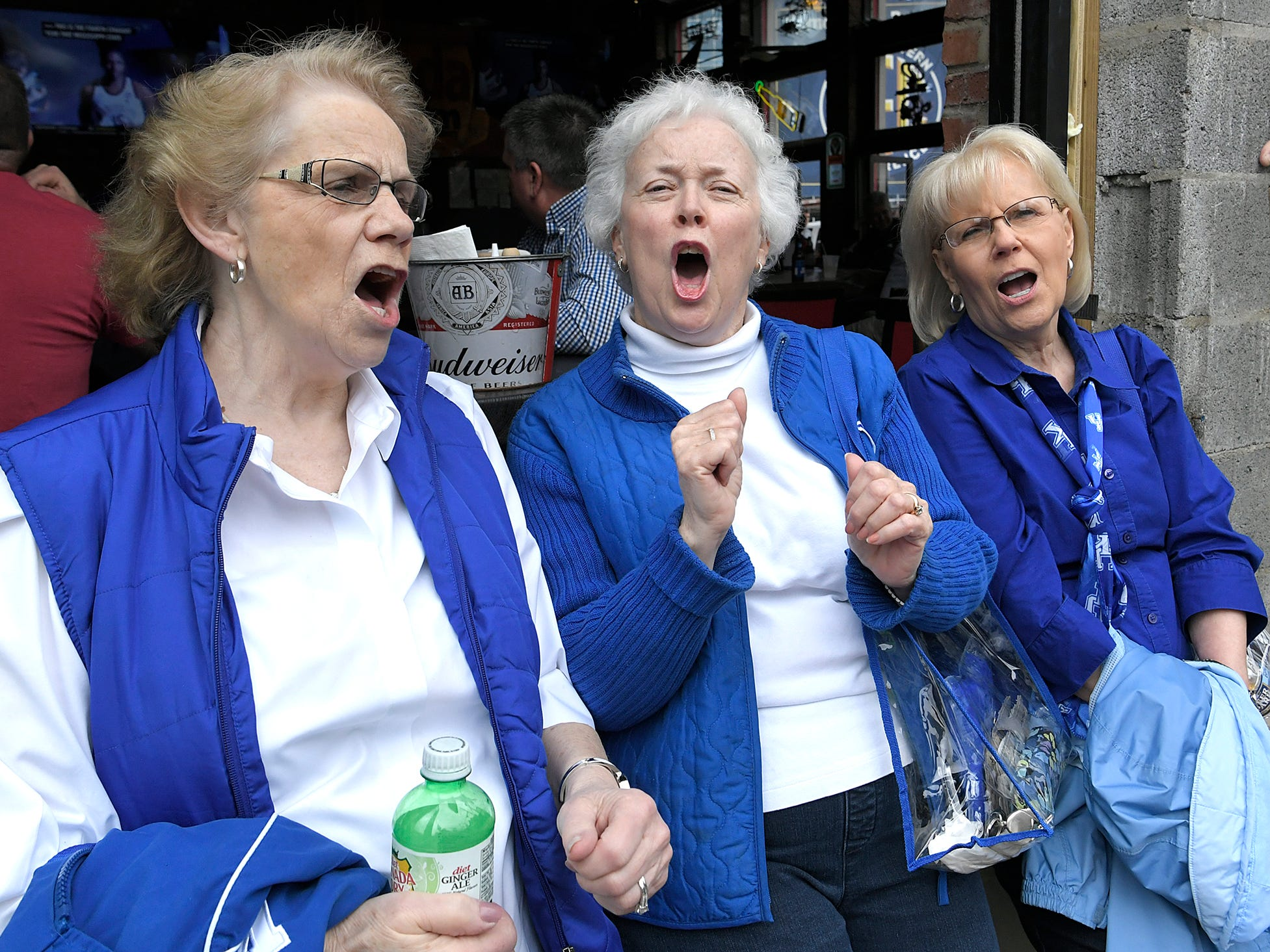 Kentucky fans Faye Warfield, Dee Hayes and Anna Raines yell a team cheer on Broadway during the SEC Mens Basketball Tournament in Nashville on Thursday, March 14, 2019.