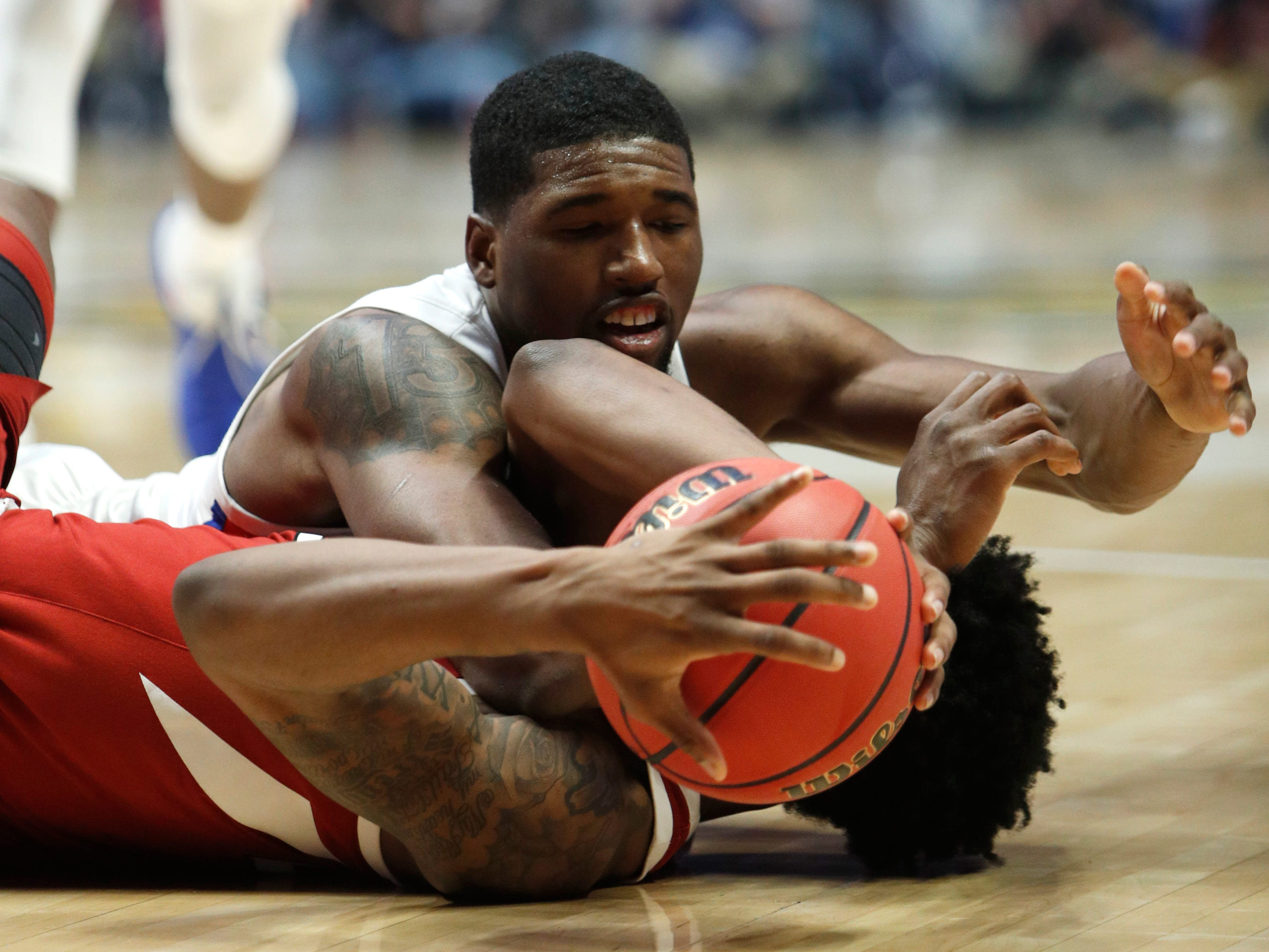 Florida center Kevarrius Hayes (13) and Arkansas forward Gabe Osabuohien (22) battle for the ball during the second half of the SEC Men's Basketball Tournament game at Bridgestone Arena in Nashville, Tenn., Thursday, March 14, 2019.
