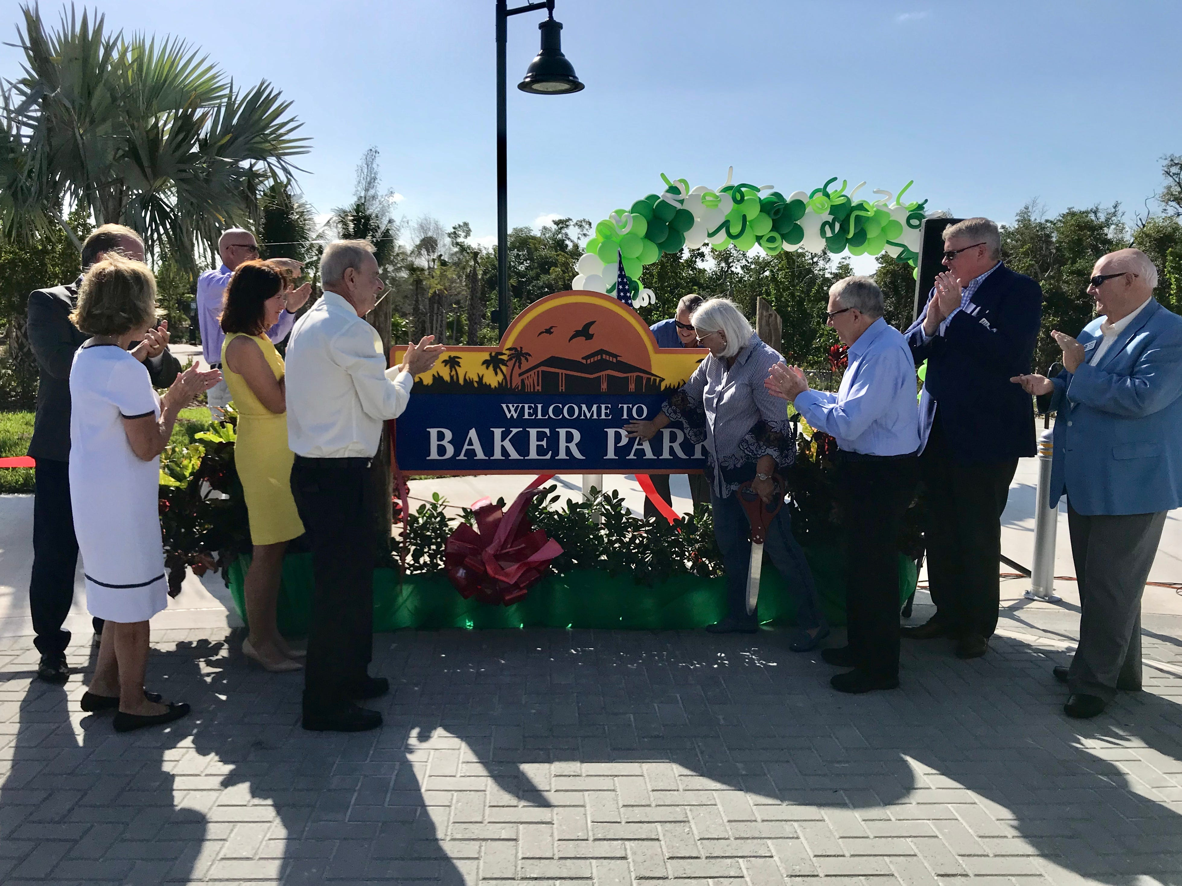 Patty Baker, right, touches the Baker Park sign during the dedication ceremony on March 14, 2019. The first portion of Baker Park opened on March 14. The rest of the park is set to open in October.
