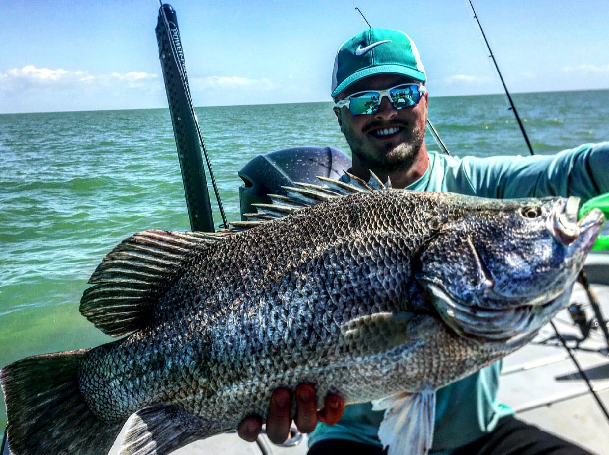 Kenny from South Dakota with a stud tripletail using squid while fishing with Capt. Christian Sommer.