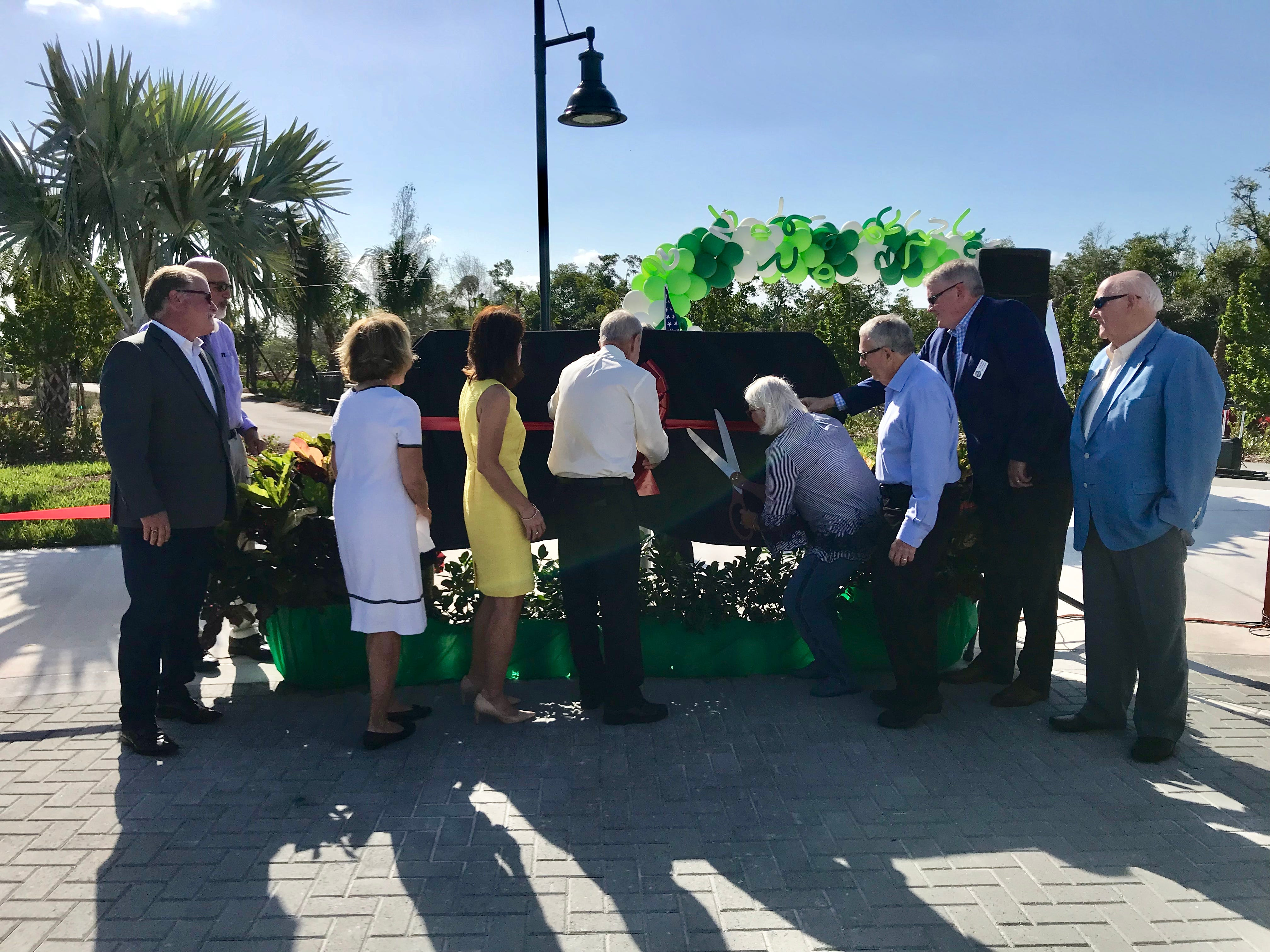 Patty Baker, right, cuts the ribbon on the Baker Park sign during the dedication ceremony on March 14, 2019. The first portion of Baker Park opened on March 14. The rest of the park is set to open in October.