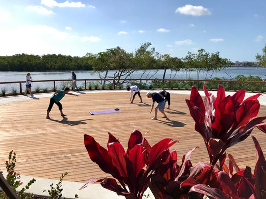 A yoga class practices on the sunrise terrace in Baker Park on Thursday, March 14, 2019, the day the first portion of the long-awaited park opened. The rest of the park is set to open in October.