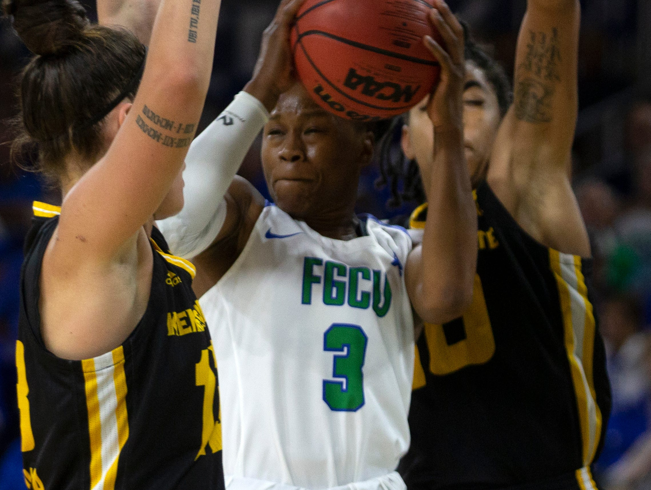 Florida Gulf Coast University's Keri Jewett-Giles attempts a layup between Kennesaw State's Carlotta Gianolla, left, and Alexis Poole, Wednesday, March 13, 2019, at Florida Gulf Coast University's Alico Arena.