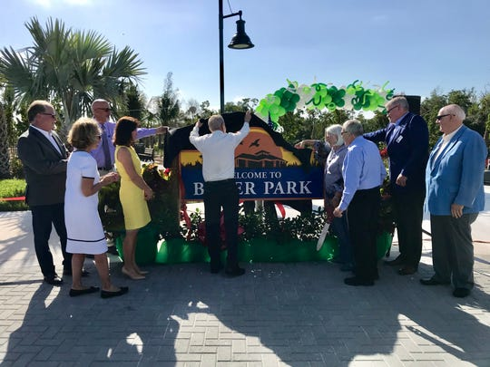 Mayor Bill Barnett, center, unveils the Baker Park sign during the dedication ceremony opening the first portion of Baker Park on Thursday, March 14, 2019. The rest of the park is set to open in October.