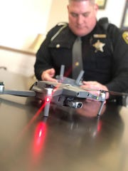 A Licking County sheriff's deputy holds the controls of the agency's new drone during a drone flight ceremony on Monday, March 11, 2019.