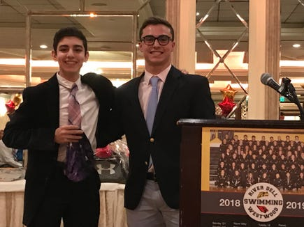 Peter Akdemir, left, accepts the Purple Speedo from senior Alec Balasny at the River Dell/Westwood swim banquet.