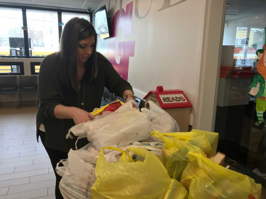 Erica Bixby, director of operations, sorts books for pickup at 10 locations for Boys and Girls Club of Paterson and Passaic