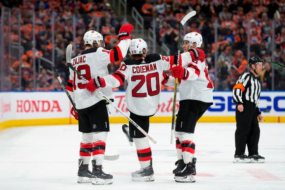 New Jersey Devils' Travis Zajac (19), Blake Coleman (20) and Steven Santini (16) celebrate Coleman's goal against the Edmonton Oilers during the third period of an NHL hockey game Wednesday, March 13, 2019, in Edmonton, Alberta. (Codie McLachlan/The Canadian Press via AP)