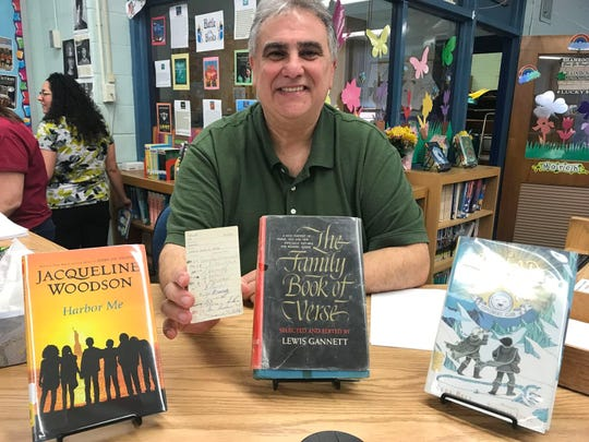 """Vice Principal Dominick Tarquinio of Memorial Middle School shows off the library card from """"The Family Book of Verse,"""" an overdue library book that was returned after more than 55 years."""