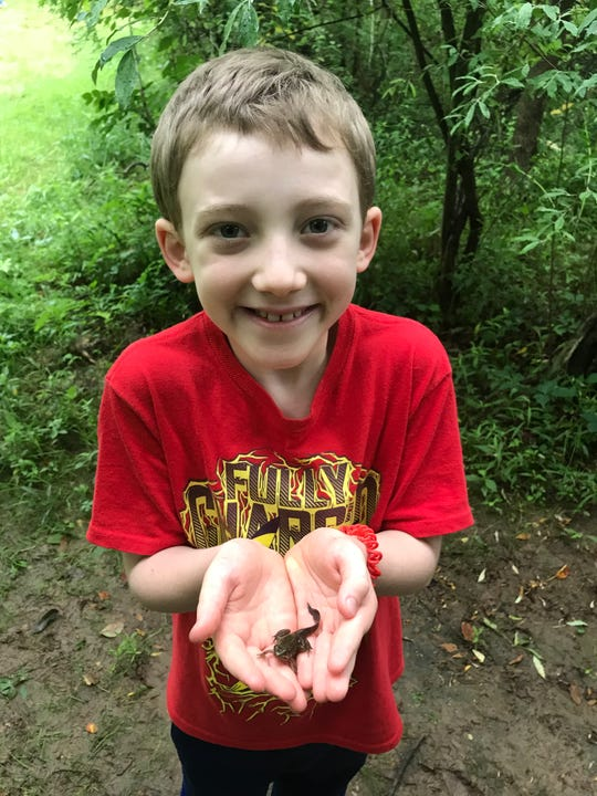 Caleb Van de Voort, who died suddenly of an asthma attack on Jan. 7, holds a frog that he caught during a camping trip with Wayne Cub Scout Pack 108.