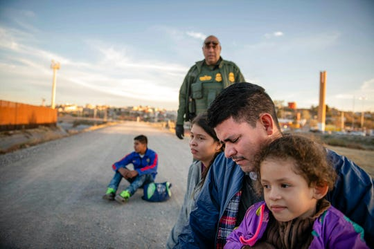 This photo taken March 4, 2019, shows Jose Francisco Juárez and his daughters, 5-year-old Perla Victoria and 17-year-old Helen, who traveled from Honduras to ask for asylum in the United States. They were part of a group of Central American migrants that included a teenager, left, traveling alone from Honduras. All waited for Border Patrol to transport them to a processing center in El Paso.