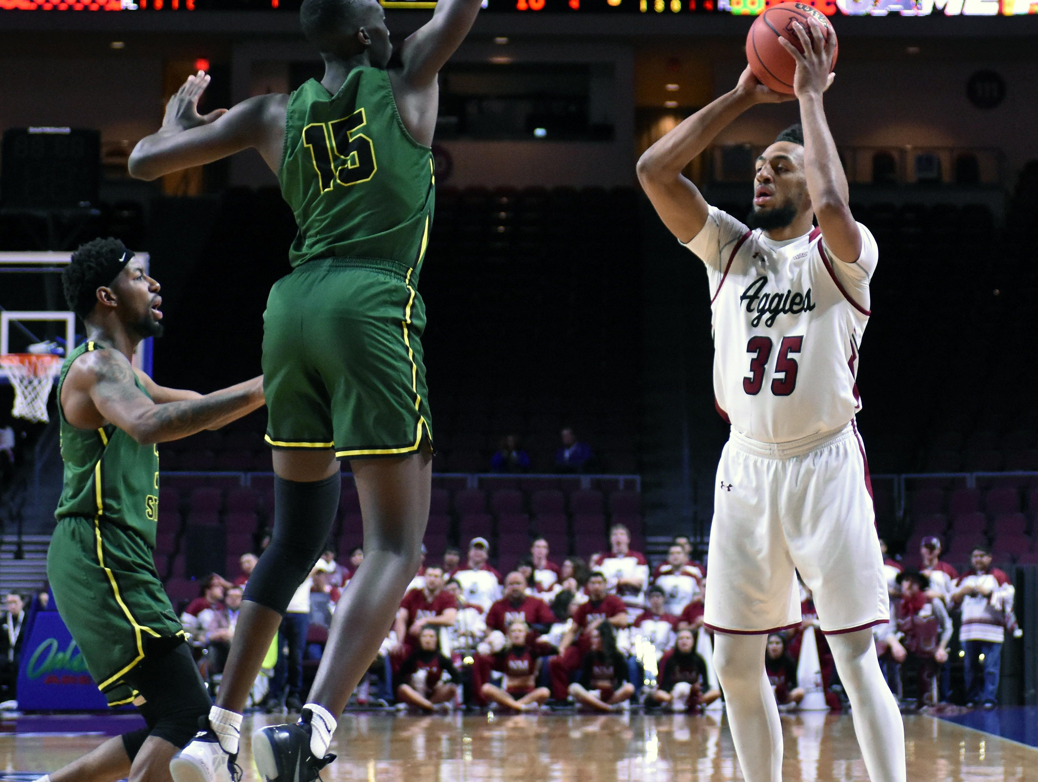 New Mexico State's Johnny McCants looks to make a pass as Chicago State's Noah Bigirumwami closes on him in the first half a WAC Tournament first-round game Thursday, March 14, 2019, at the Orleans Arena in Las Vegas, Nevada.