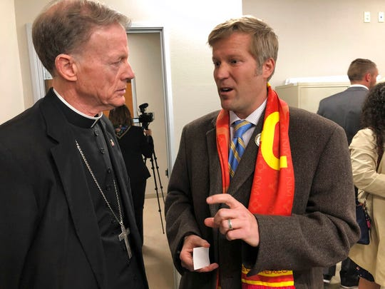 """Santa Fe Archbishop John Wester, left, talks to Albuquerque Mayor Tim Keller, right, at Catholic Charities in Albuquerque, N.M., on Wednesday, March 13, 2019. Keller announced Wednesday that """"hundreds"""" of migrants from Central America and Brazil are expected to arrive in the city in the coming weeks and volunteers are preparing for visitors."""