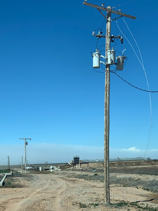 Damaged power lines blow in the wind near Dexter, New Mexico Wednesday.