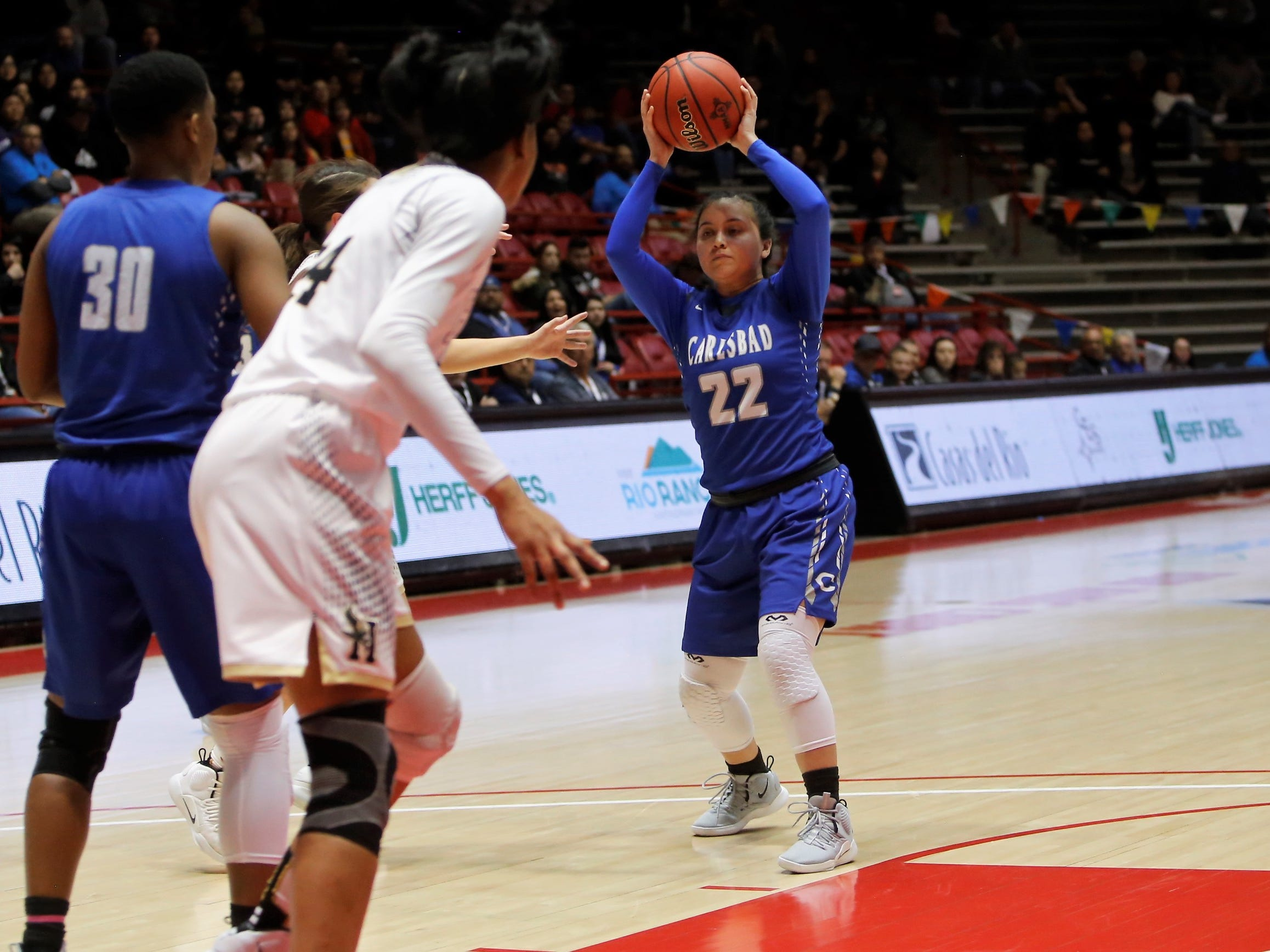 Carlsbad's Nyah Chacon looks to pass the ball to teammate Dayshaun Moore (30) against Hobbs during Thursday's 5A state semifinals at Dreamstyle Arena in Albuquerque.