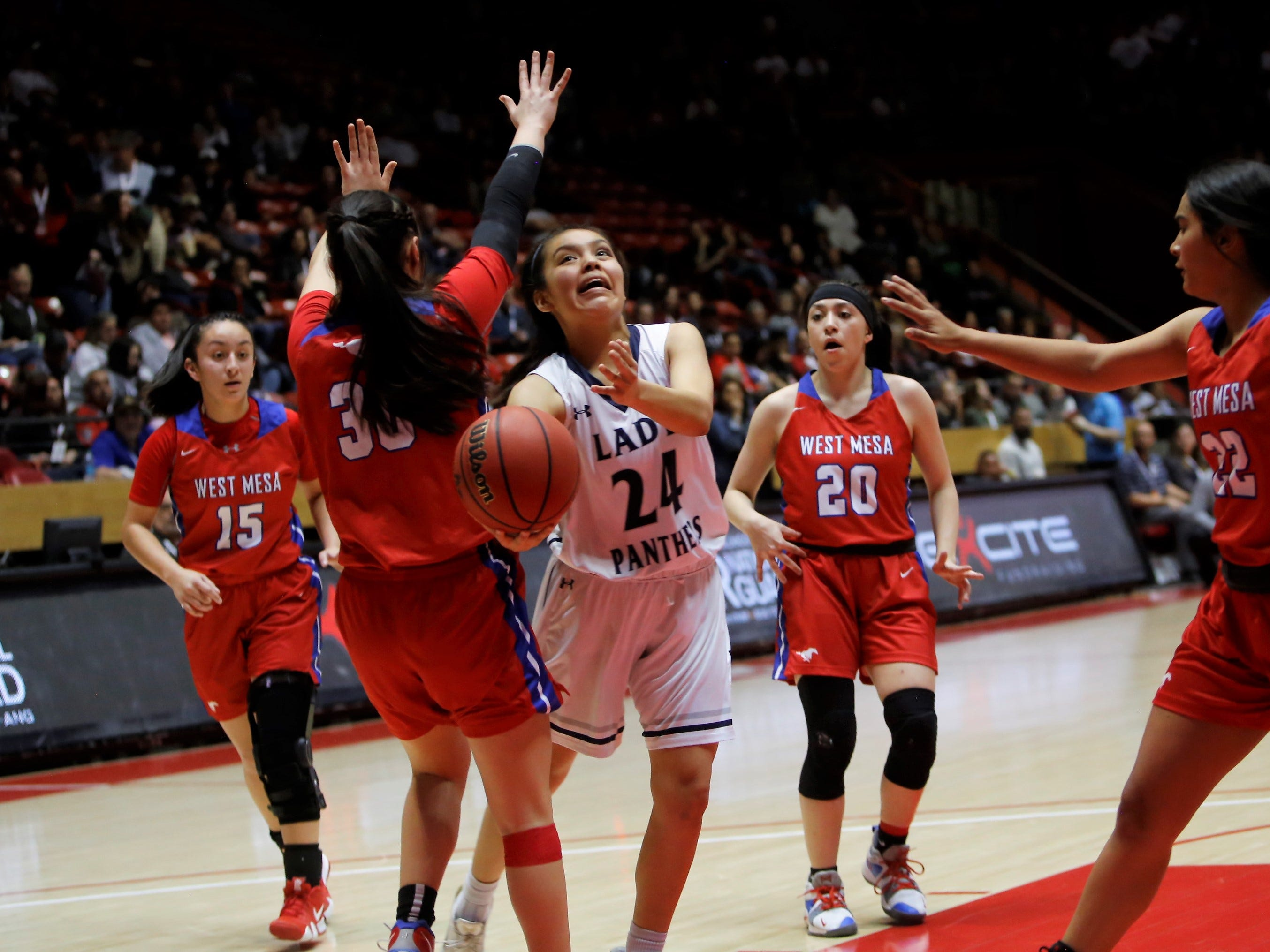 Piedra Vista's Tai Tai Woods attacks the basket and gets fouled by West Mesa's Jazmine Cordova (30) during Thursday's 5A state semifinals game at Dreamstyle Arena in Albuquerque.