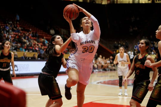 Kirtland Central Siigrid Lii'bilnaghahi attacks the basket Española Valley's Kaylinn Martinez (23) during Thursday's 4A state semifinals at Dreamstyle Arena in Albuquerque.