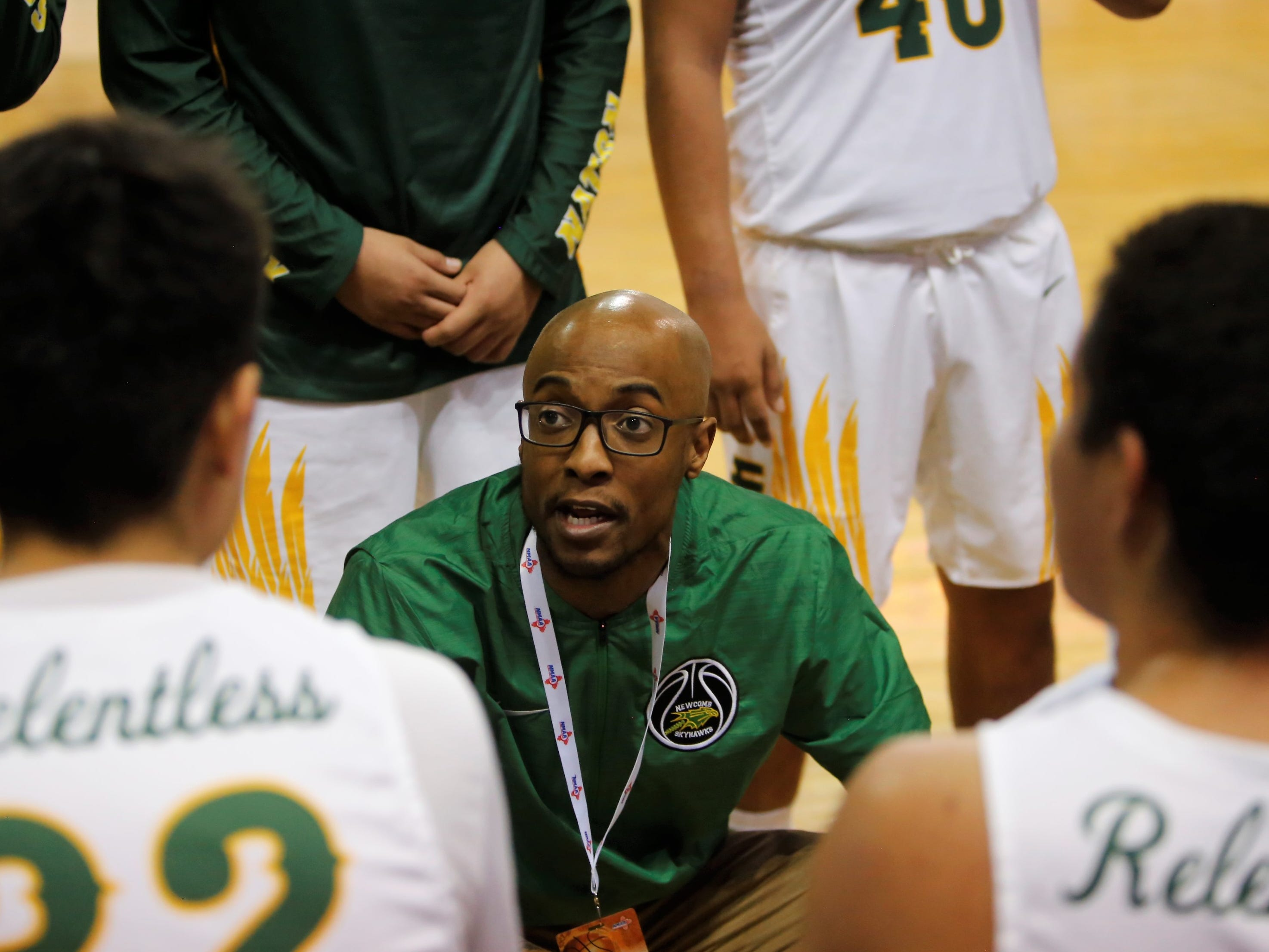 Newcomb coach Dominique Richardson talks to his team in-between quarters against McCurdy during Wednesday's 2A state quarterfinals at the Santa Ana Star Center in Rio Rancho.