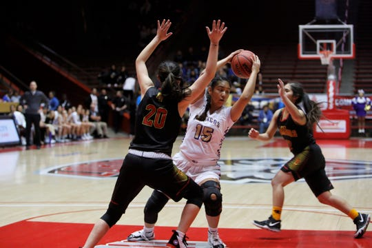 Kirtland Central's Aubrey Thomas looks to pass the ball down the left side against Española Valley's Destiny Valdez (20) during Thursday's 4A state semifinals at Dreamstyle Arena in Albuquerque.