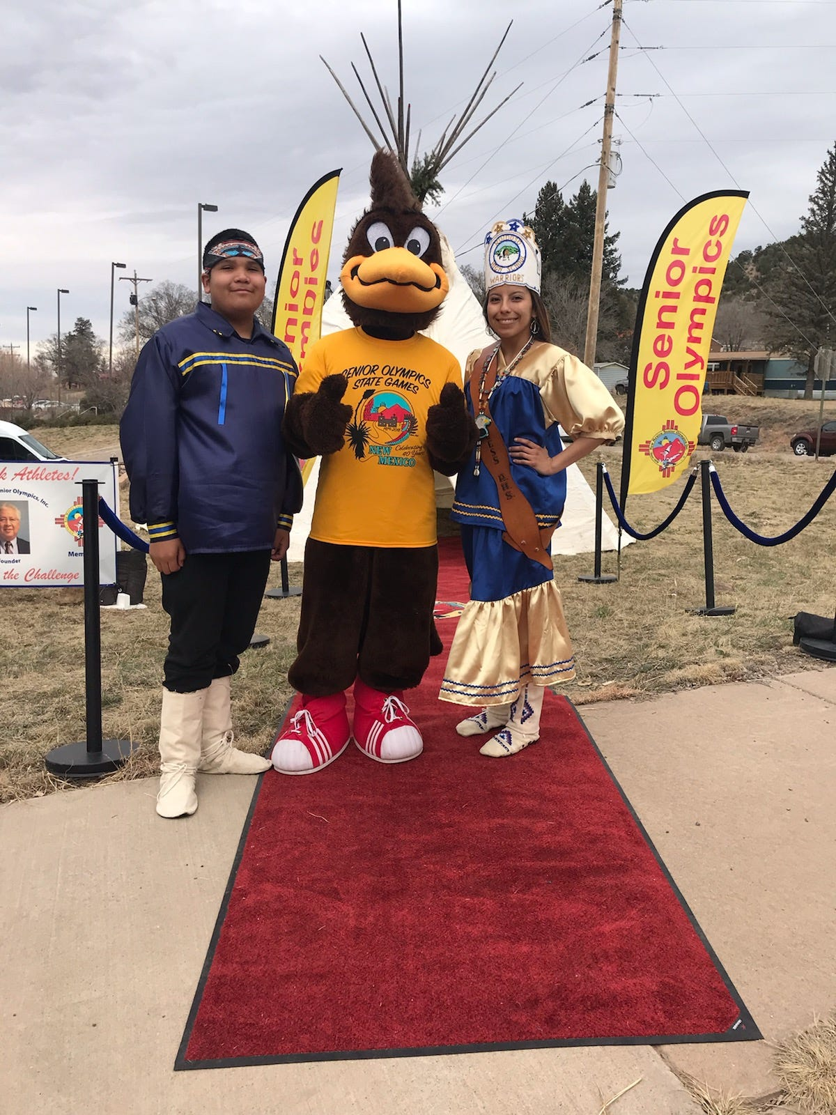 Ruidoso school Brave and Princess take time to pose with the Senior Olympics Mascot, the Road Runner.