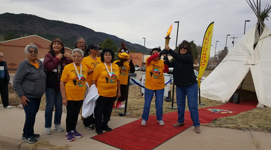 The torch relay and senior Olympics competitors at the Mescalero Elderly Center during a celebration for the upcoming Nationals this summer.
