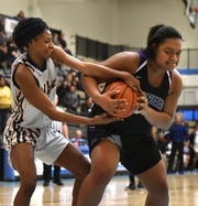 Wayne Memorial player Sammiyah Hoskin, left, battles with Ann Arbor Pioneer Asaria Turman for a rebound on March 13.