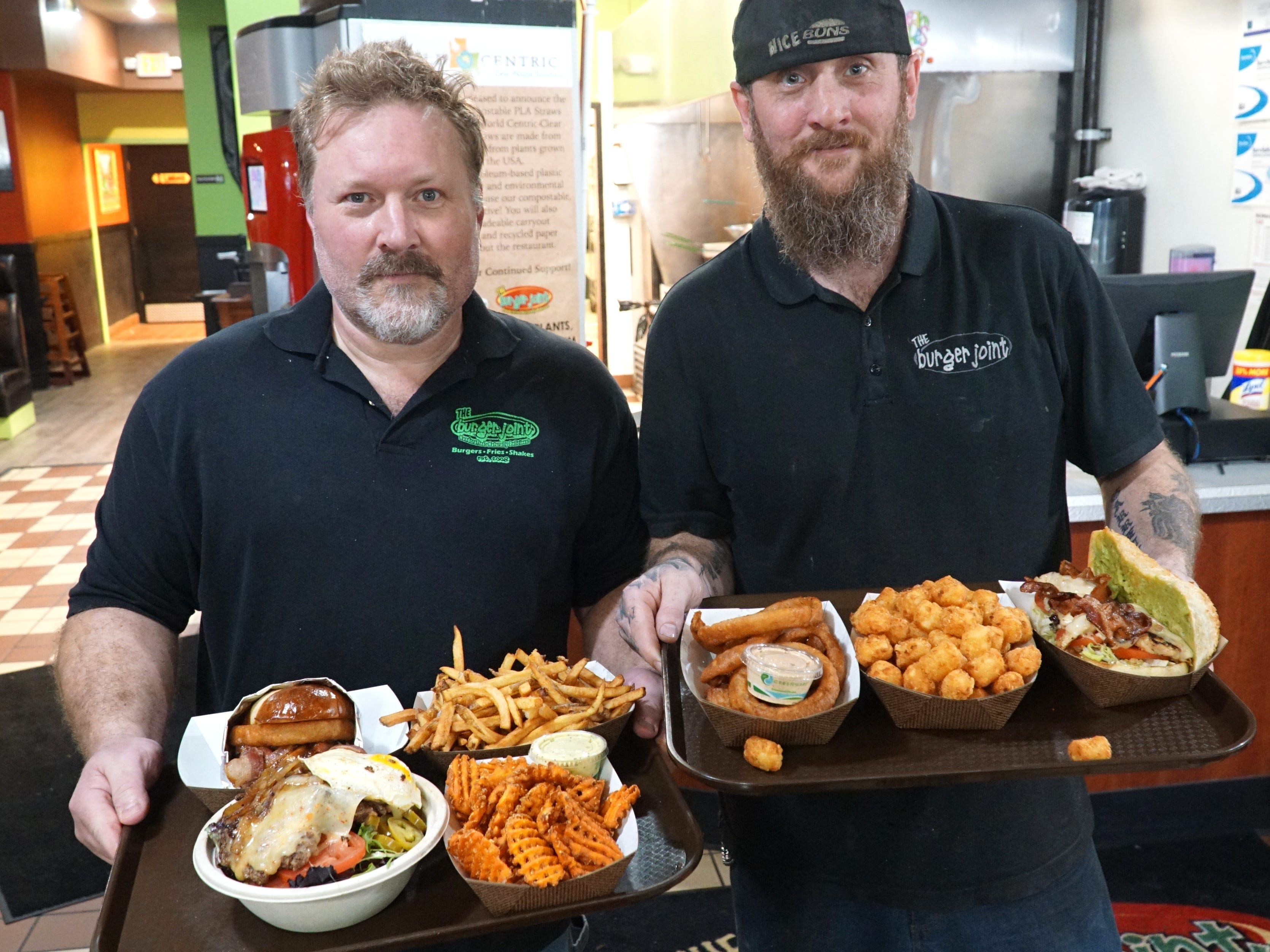 Milford Burger Joint co-operators Jason Monarch, left, and Brian Belwood show off two trays of some of their fare including a bacon cheeseburger on a brioche bun (and an onion ring kicker), waffle-cut sweet potatoes, fries, onion rings and tater tots, and a chicken-avacado club sandwich.