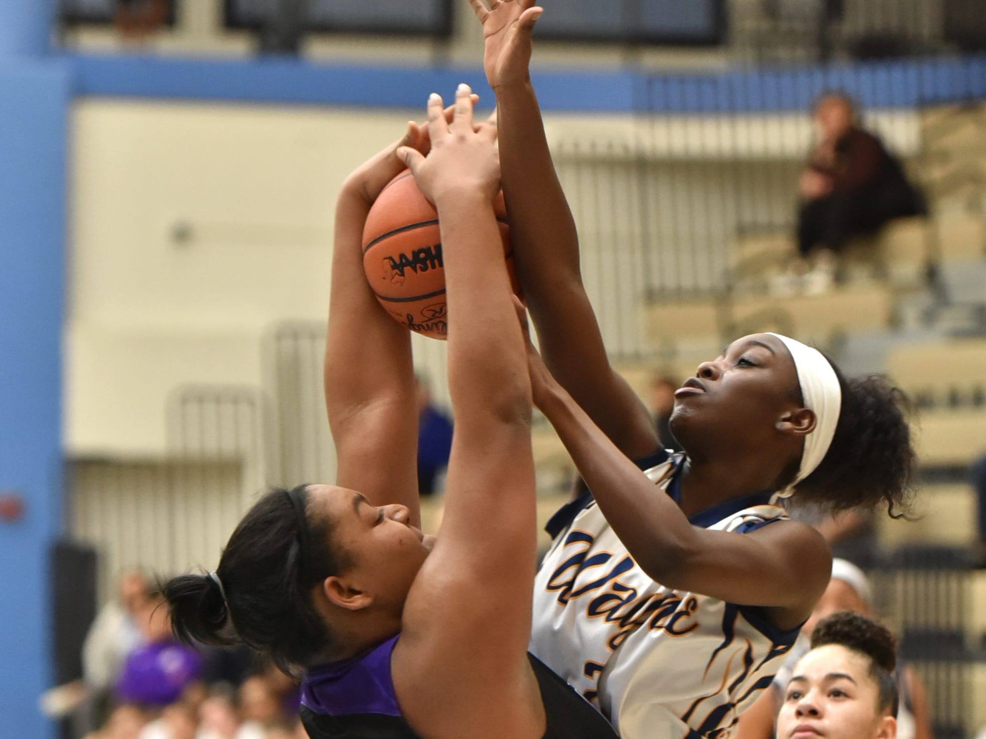 "5'6"" Zebra Jordan Wright tries to rip a rebound away from 6' Pioneer Asaria Turman."
