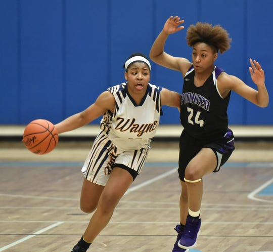 As Pioneer Ilena Garett, right, tries to guard her - Wayne Memorial player Jeanae Terry drives for the basket.