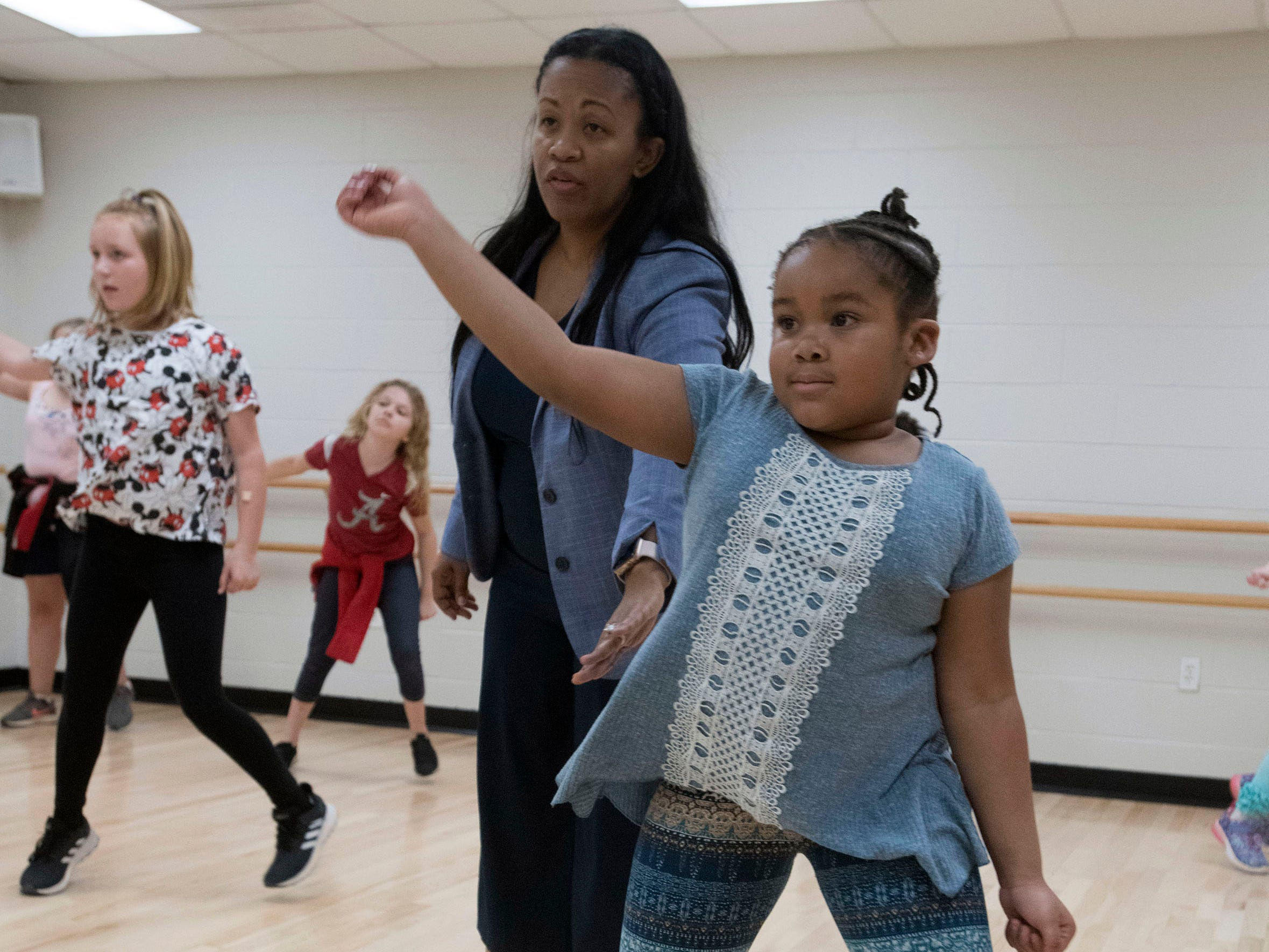 Joy Gainer help to teach Janelle Williams, 6, and other children a few hip hop dance moves during a class at the Gull Point Community Center on Spanish Trail on Wednesday, March 13, 2019.