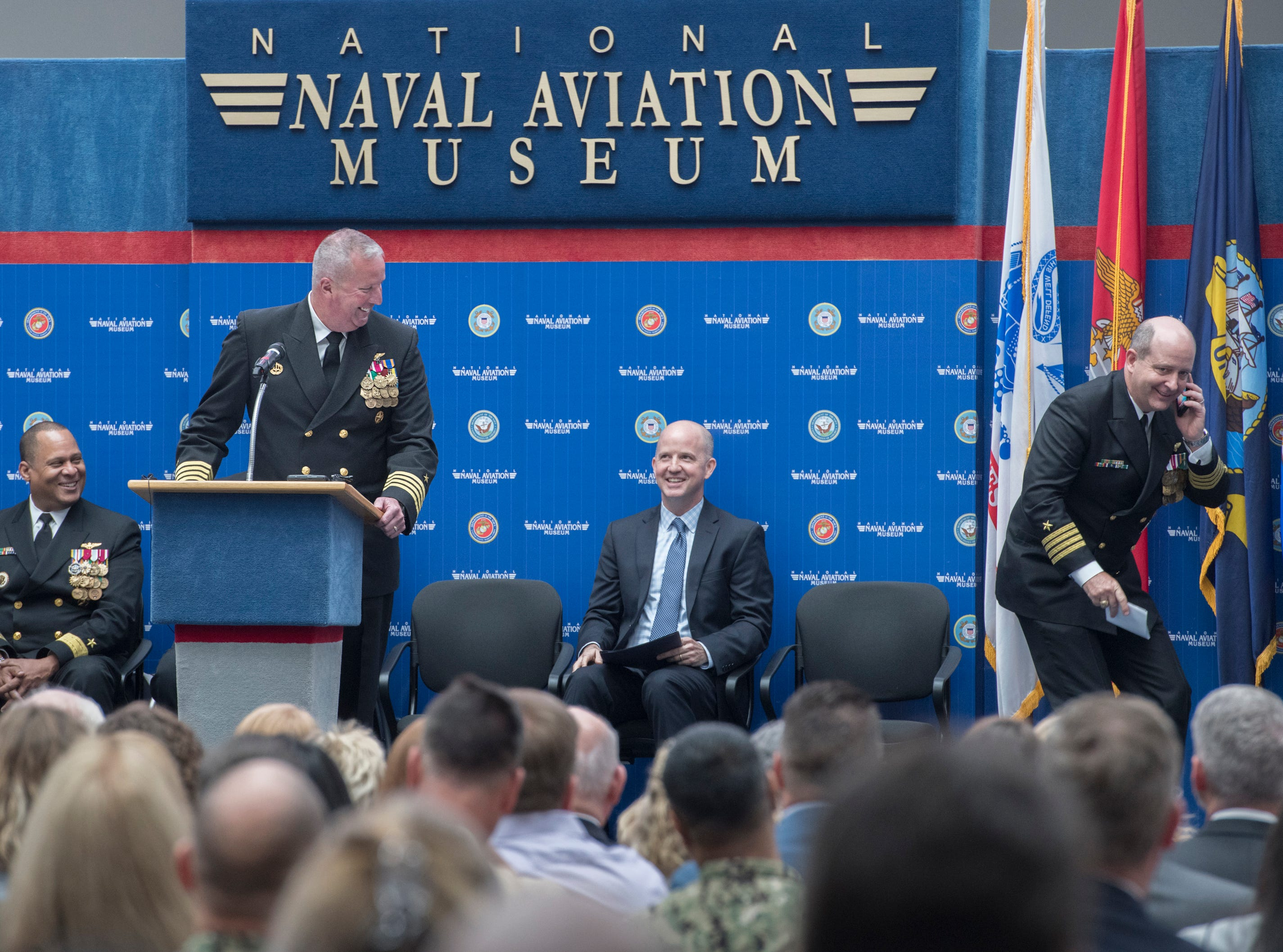 New base commander Capt. Timothy Kinsella, Jr., right, jokely pretends to take a phone call while outgoing commander Capt. Christopher Martin speaks during the change of command ceremony at the National Naval Aviation Museum at Naval Air Station Pensacola on Thursday, March 14, 2019.