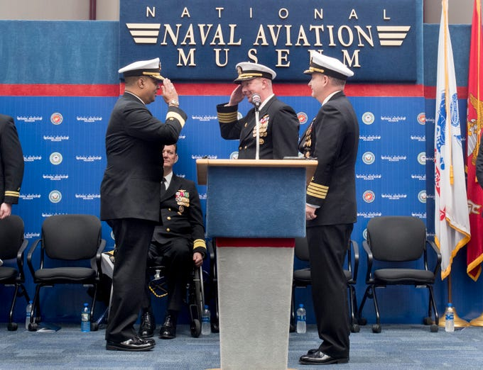 New base commander Capt. Timothy Kinsella, Jr., right, looks on as outgoing commander Capt. Christopher Martin, center, and Rear Adm. Gary Mayes  exchange salutes during the change of command ceremony at the National Naval Aviation Museum at Naval Air Station Pensacola on Thursday, March 14, 2019.