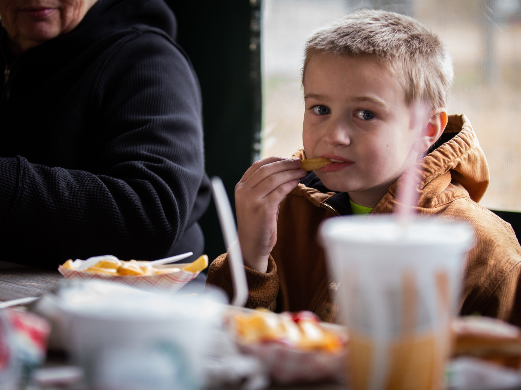 Mason Light, 8, munches on a fry during Tropical Treat's first day of business for the 2019 season, Wednesday, March 13, 2019, in Berwick Township.