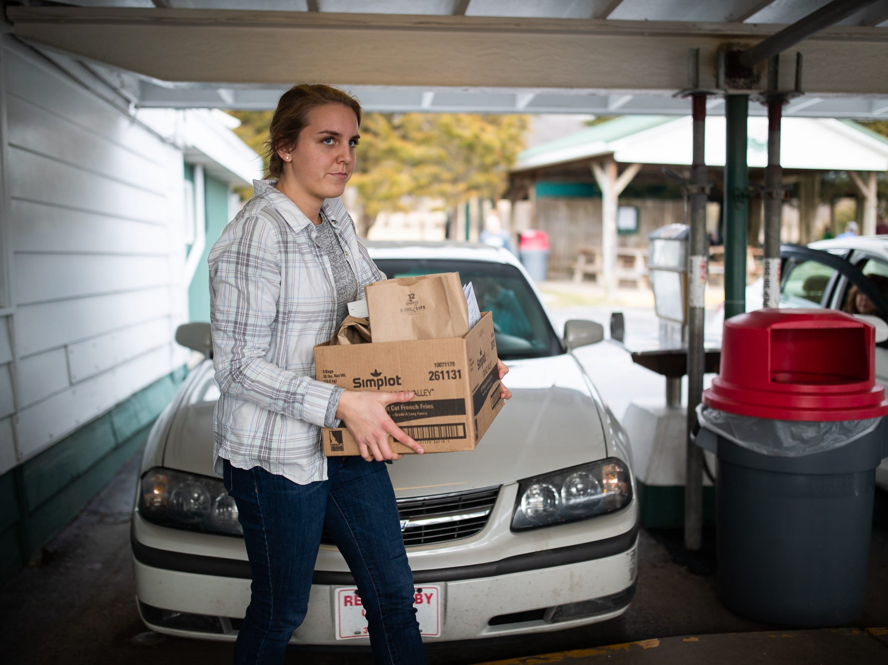 Employees carry food orders to customers during Tropical Treat's first day of business for the 2019 season, Wednesday, March 13, 2019, in Berwick Township.