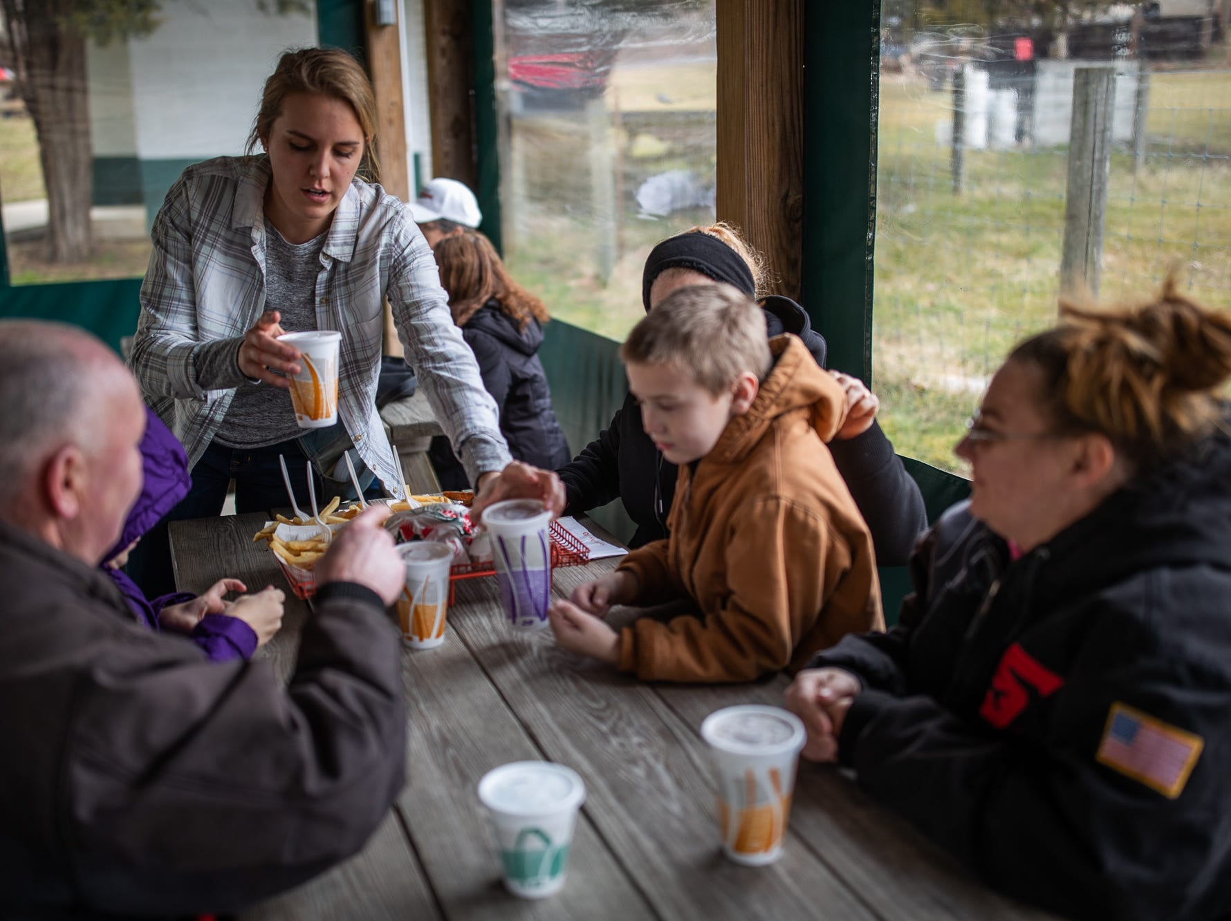 An employee drops off the order of David Light, left, Trevor Light, 11, second from left behind David, Sharon Light, third from right, Mason Light, 8, second from right, and Terrie Light, right, during Tropical Treat's first day of business for the 2019 season, Wednesday, March 13, 2019, in Berwick Township.