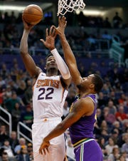Phoenix Suns center Deandre Ayton (22) shoots over Utah Jazz forward Derrick Favors during the second half of an NBA basketball game Wednesday, March 13, 2019, in Phoenix. (AP Photo/Matt York)