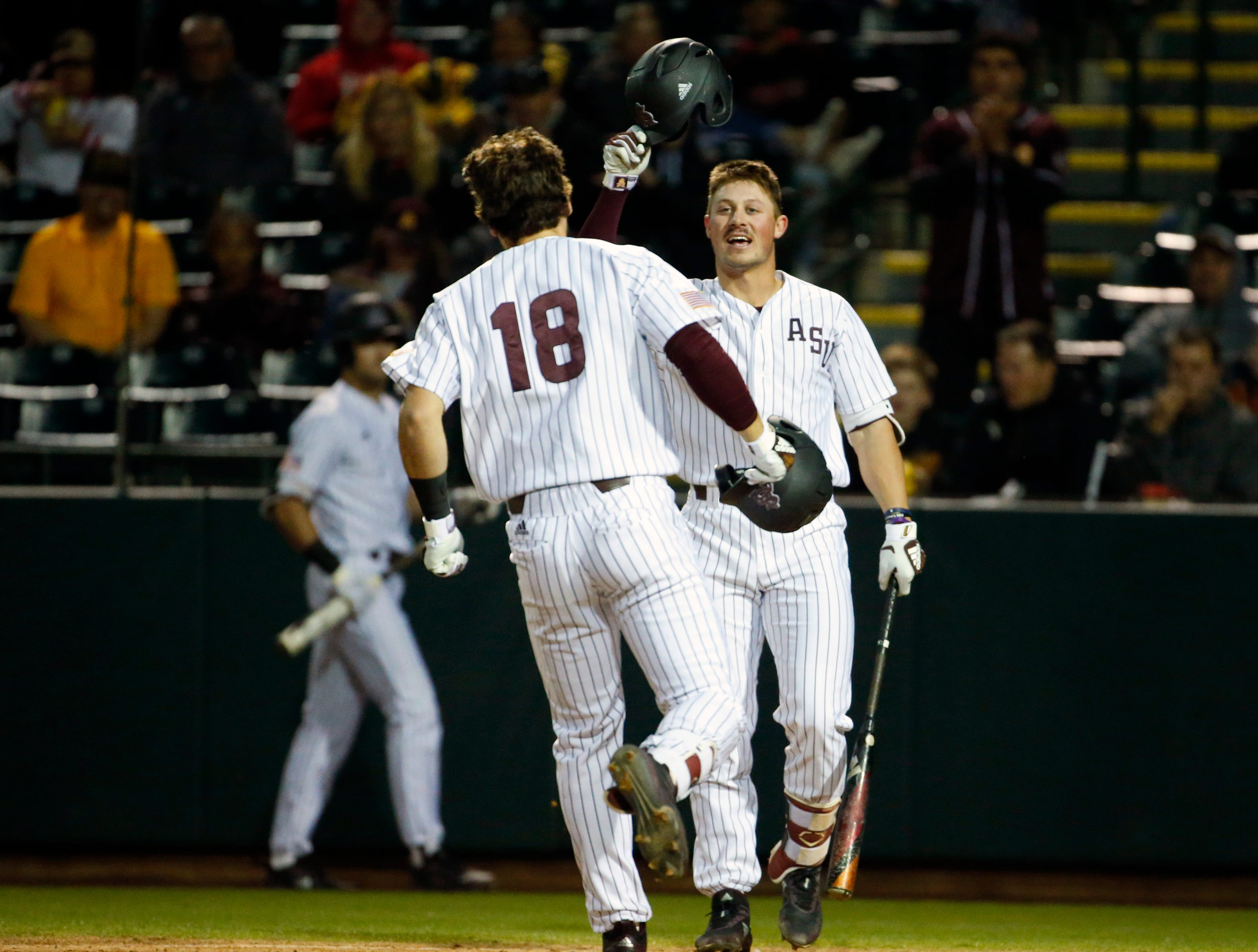ASU left fielder Trevor Hauver (18) celebrates his homer with teammate first baseman Spencer Torkelson (20) during a baseball game against New Mexico at Phoenix Municipal Stadium on March 13, 2019.