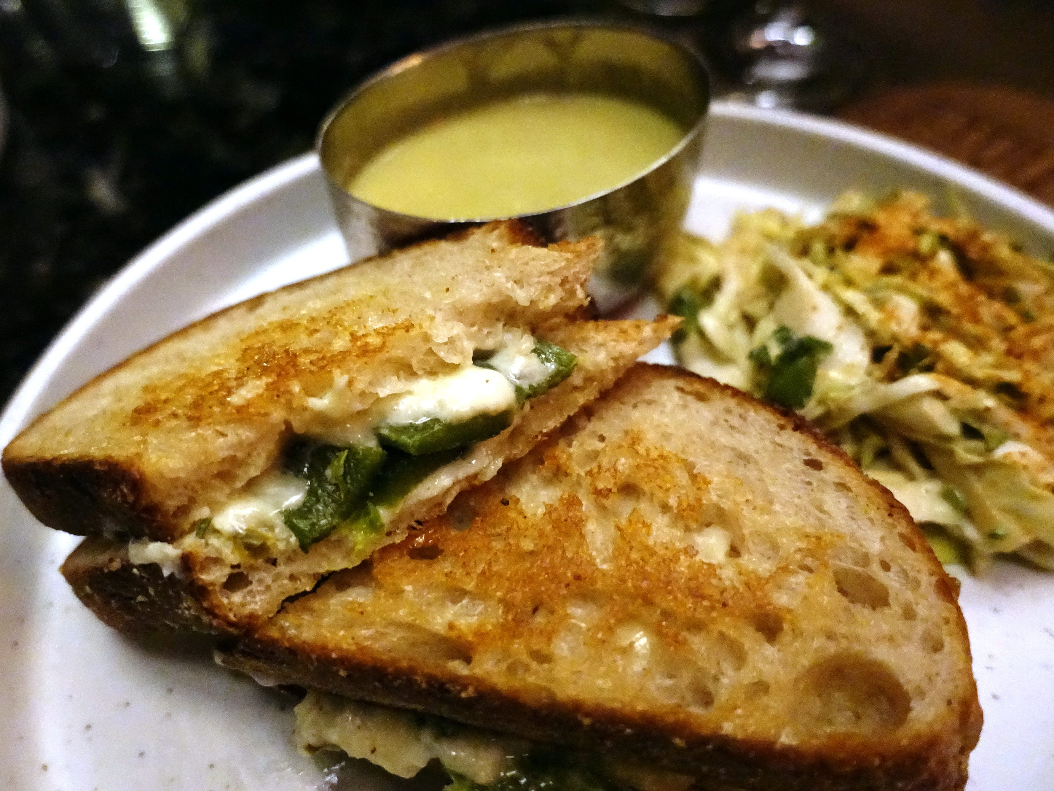 Rajas grilled cheese with roasted poblanos, red bell peppers, onion and corn crema, Monterey jack, asadero, queso chihuahua and green tomato dip at Little Rituals in Phoenix.