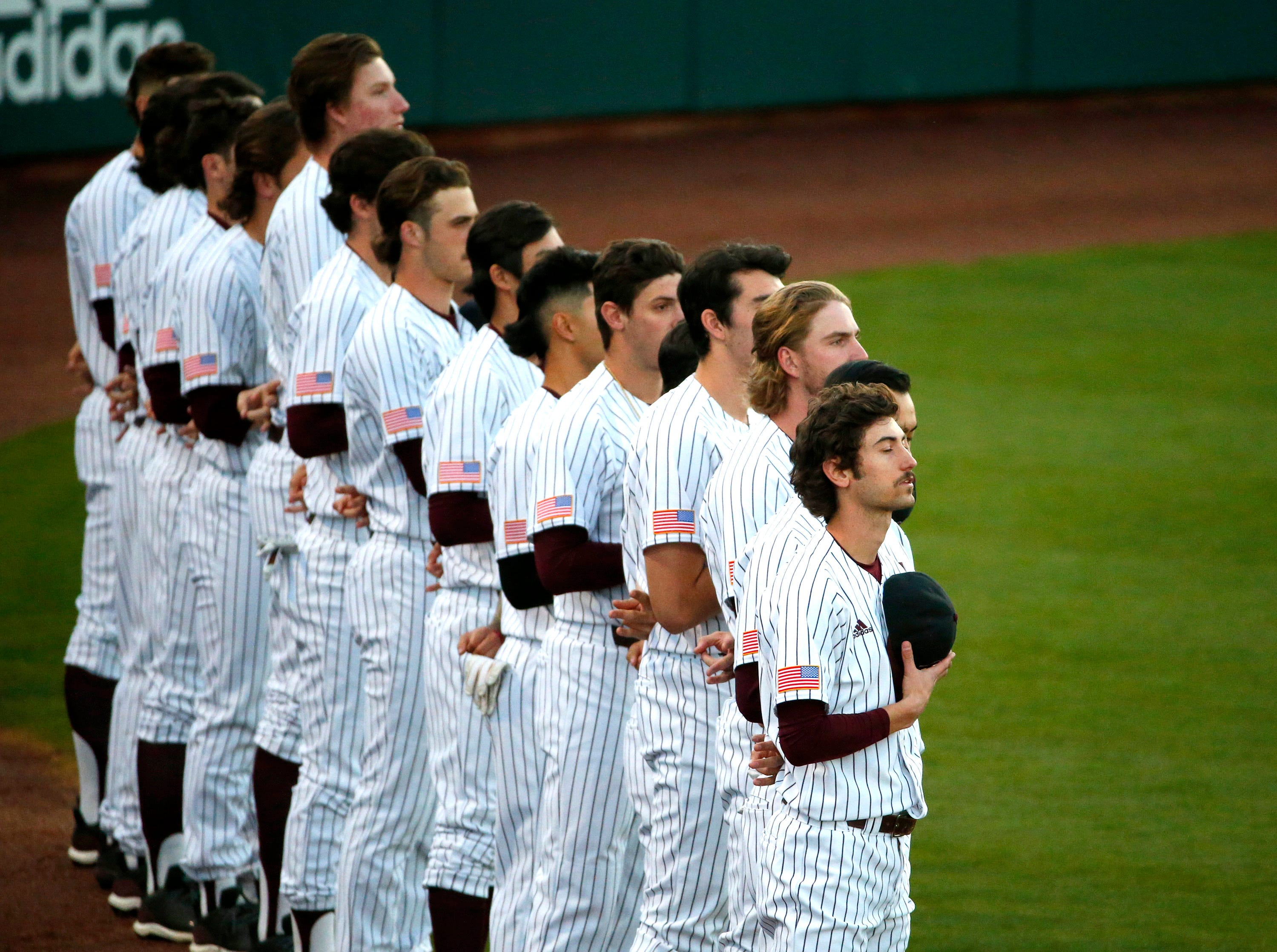 ASU stands for the National Anthem before a baseball game against New Mexico at Phoenix Municipal Stadium on March 13, 2019.