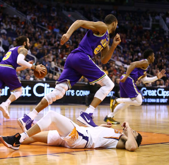 Phoenix Suns guard Devin Booker (1) lays on the court  during a Utah Jazz fast-break in the second half on Mar. 13, 2019 at Talking Stick Resort Arena in Phoenix, Ariz.