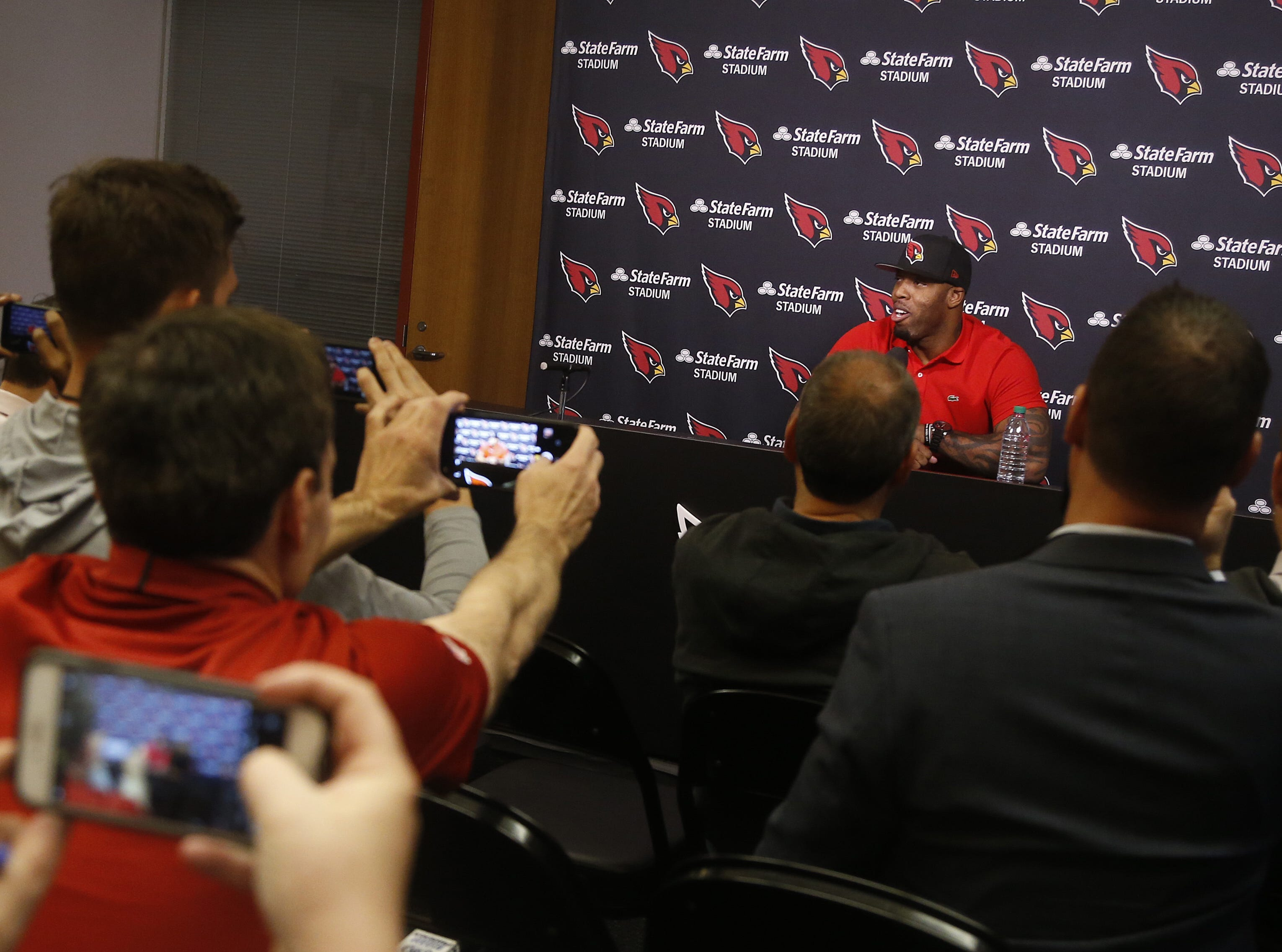 Reporters take pictures of Terrell Suggs as he speaks with the media during his introductory press conference at the Arizona Cardinals Training Facility in Tempe, Ariz. on March 14, 2019.
