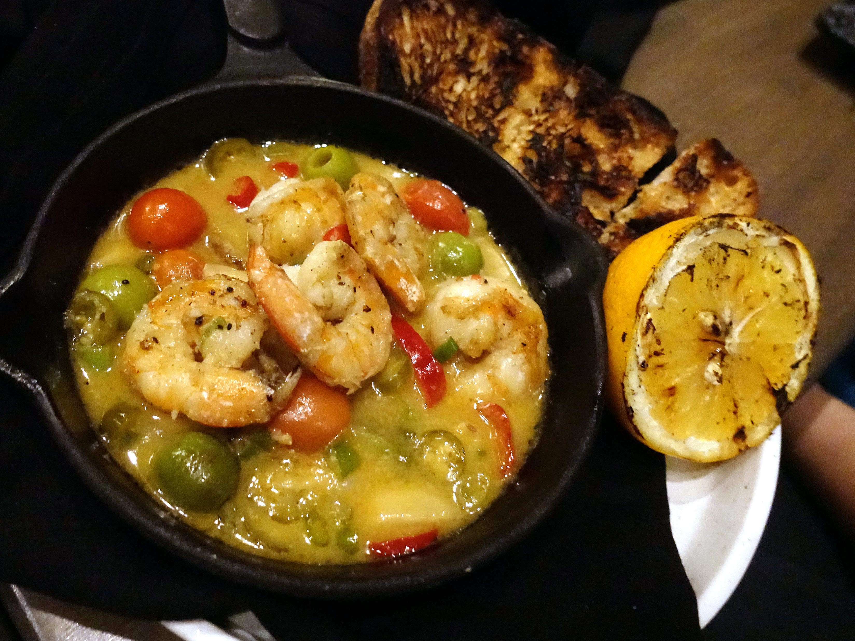 Wild gulf shrimp with roasted garlic, scallion, tomatoes, Castelvetrano olives, herbs, white wine and grilled Noble bread at Little Rituals in Phoenix.