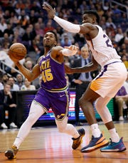 Utah Jazz guard Donovan Mitchell (45) drives as Phoenix Suns center Deandre Ayton defends during the first half of an NBA basketball game Wednesday, March 13, 2019, in Phoenix. (AP Photo/Matt York)