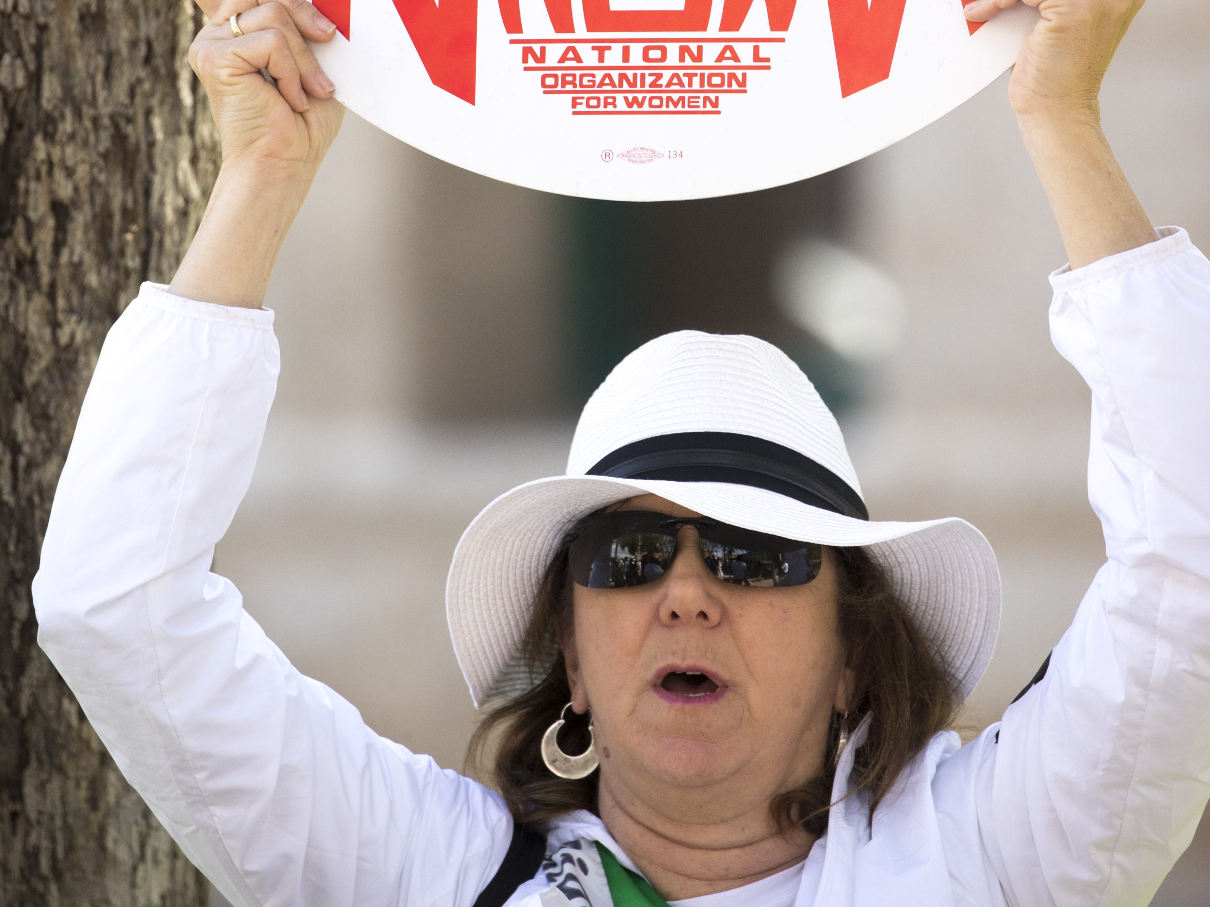 Lisa Bishop holds a sign during an ERA rally in the Rose Garden, March 13, 2019, at the Arizona Capitol.